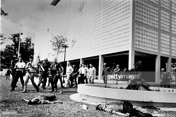 Military police reporters and US Amb Ellsworth Bunker and embassy staff walking outside US Embassy near 2 dead bodies of Vietcong people after an...