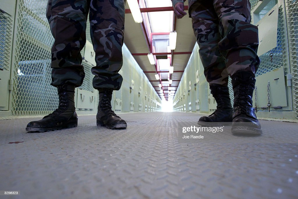 U.S. Military Police stand in a cell block in Camp Delta where detainees from the U.S. war in Afghanistan live April 7, 2004 in Guantanamo Bay, Cuba. On April 20, the U.S. Supreme Court is expected to consider whether the detainees can ask U.S. courts to review their cases. Approximately 600 prisoners from the U.S. war in Afghanistan remain in detention.