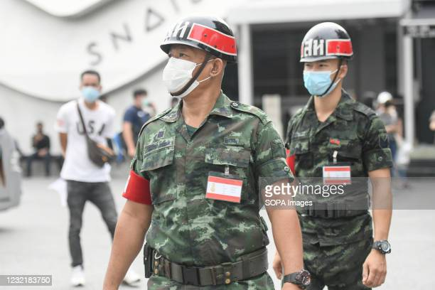 Military police stand on guard in front of biosafety mobile vehicle during a swab test drive outside a nightclub in Bangkok. The Ministry of Public...