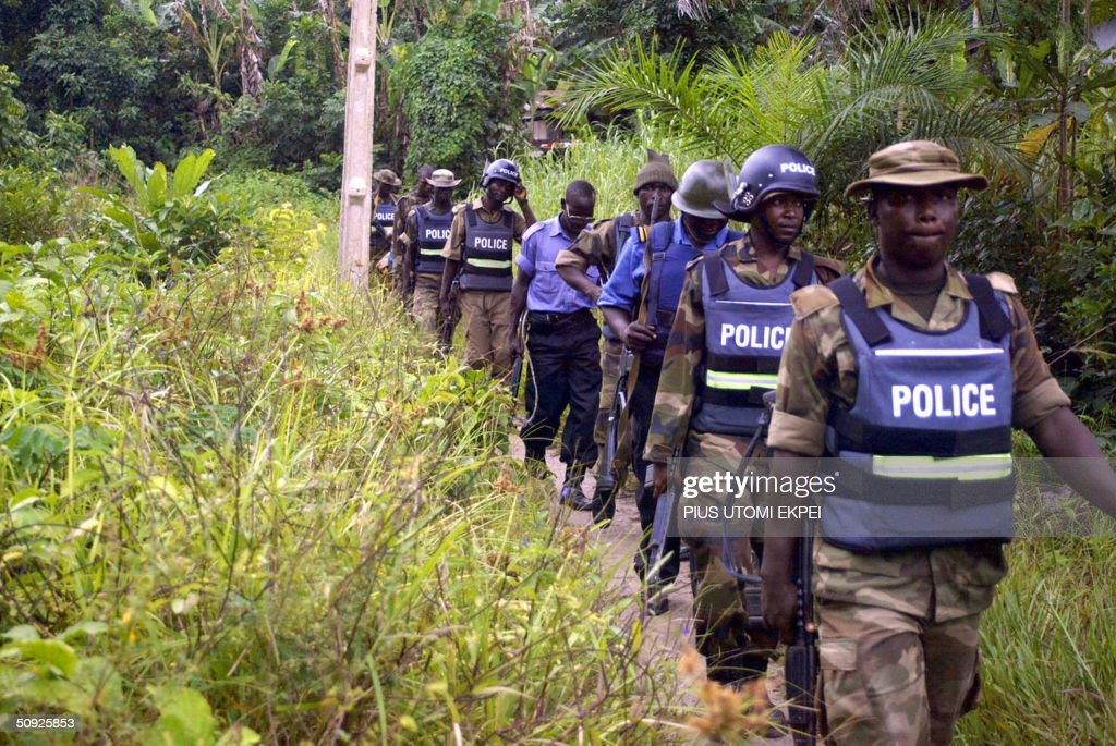 Military police walk through the bush in search of arms and criminals at Omadino community in Warri South district of the Niger Delta 04 June, 2004. Security agencies have begun house-to-house searches to check the menace of bandits and ethnic militias attacking riverine communities and oil companies.