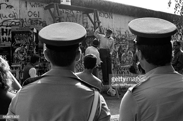 Military police watching a protest at a section of the Berlin Wall at the Brandenburg Gate West Berlin The Berlin Wall was a barrier constructed by...