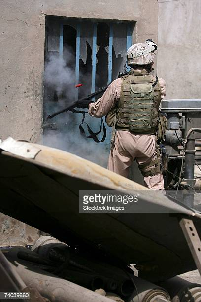 A military policeman assigned to 1st Battalion, 25th Marine Regiment, Regimental Combat Team 5, uses a breaching round to open a lock in the industrial area of Fallujah, Iraq.
