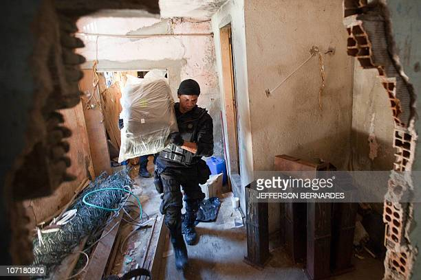 A military policeman carries a sack of drug during the raid in the Morro do Alemao shantytown on November 28 2010 in Rio de Janeiro Brazil After days...