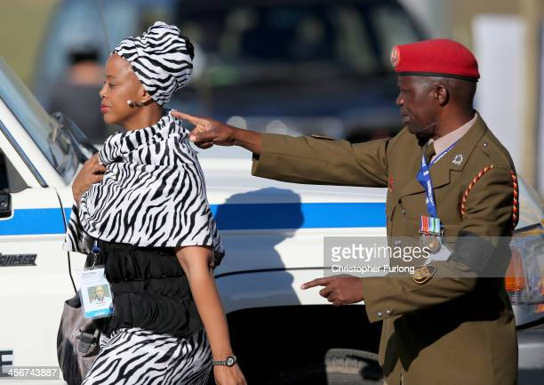 A military policeman guides a guest to the funeral of former South African President Nelson Mandela in his home village of Qunu on December 15 2013...