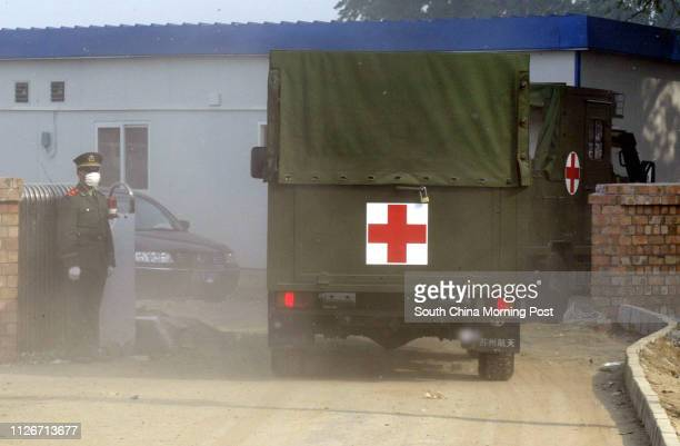 A military policeman stands guard at the entrance of the Xiaotangshan hospital as dust is kicked up by two military ambulances that enetered the...