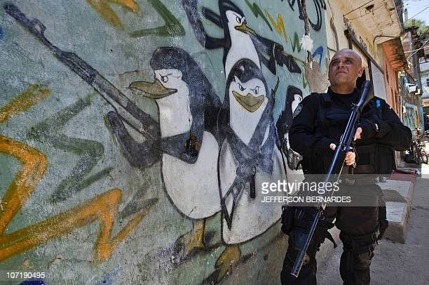 A military policeman stands guard during the raid in the Morro do Alemao shantytown on November 28 2010 in Rio de Janeiro Brazil After days of...