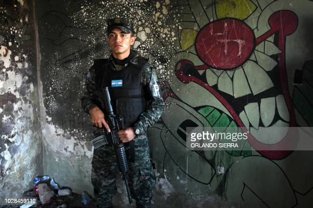 A military policeman stands guard inside a house used by gang members to commit crimes during an operation in Tegucigalpa on September 7 2018...