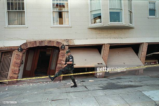 Military policeman steps over a police line on October 18 in front of a heavily-damaged building in the Marina District of San Francisco, one of the...