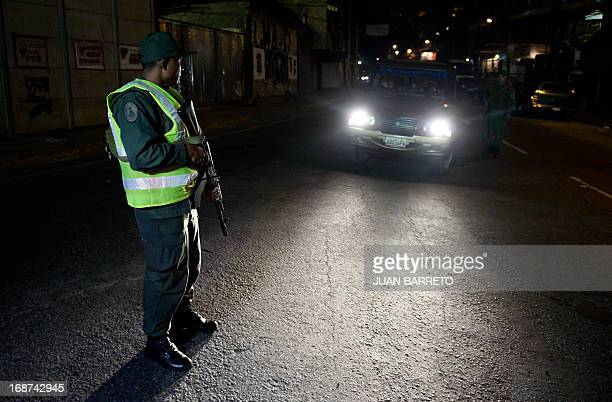 A military policeman takes part in a security operation in the impoverished Petare neighbourhood one of Caracas' most dangerous slums on May 13 2013...