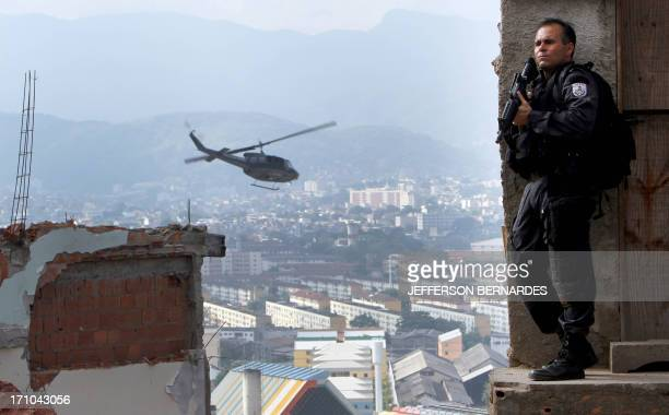 A military policeman takes position during the raid in the Morro do Alemao shantytown on November 28 2010 in Rio de Janeiro Brazil After days of...