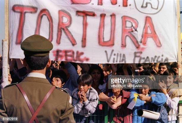 A military policeman watches part of the prodemocracy demonstrators while Pope John Paul II addresses the poor people in a suburb of Santiago 02...