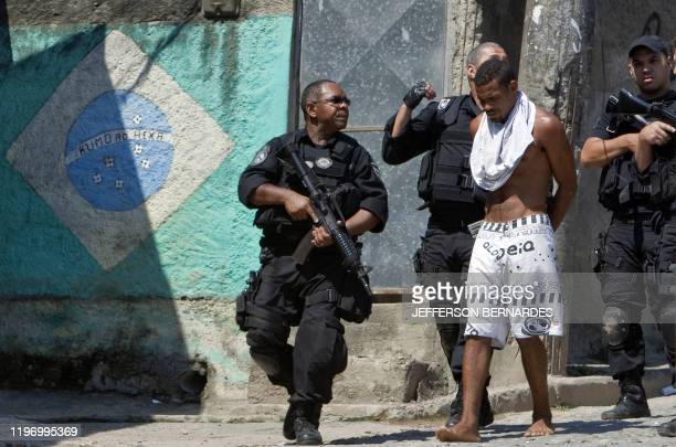 Military policemen arrest an alleged drug dealer boss during the raid in the Morro do Alemao shantytown on November 28 2010 in Rio de Janeiro Brazil...