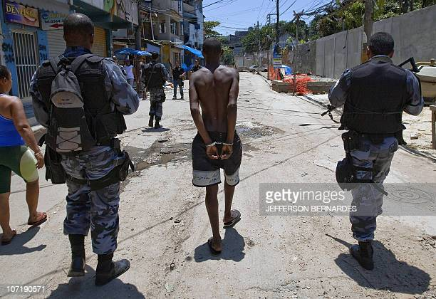 Military policemen arrest an alleged drug dealer during the raid in the Morro do Alemao shantytown on November 28 2010 in Rio de Janeiro Brazil After...