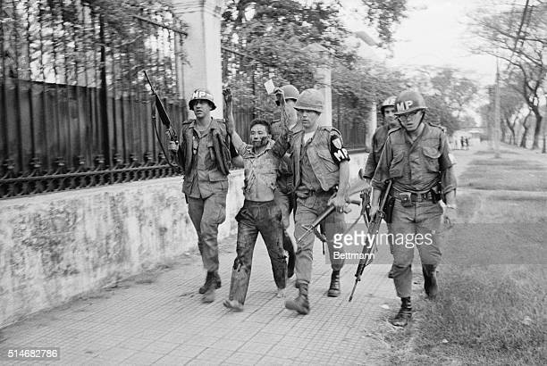 Military policemen capture a Vietcong guerrilla after a surprise attack on the United States embassy and South Vietnamese government buildings in...