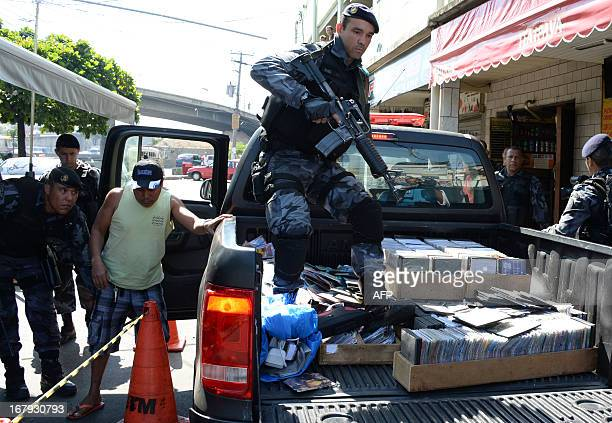 Military policemen carry pirate compact disks and drugs after arresting alleged drug dealers as they carry out an operation at Mare del Rio...