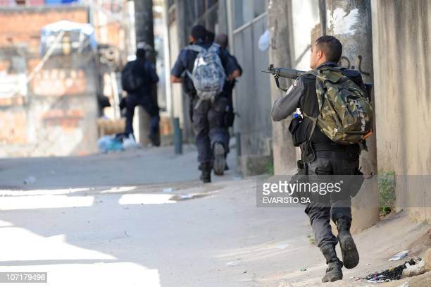 Military policemen run in an alley during the raid in the Morro do Alemao shantytown on November 28 2010 in Rio de Janeiro Brazil After days of...