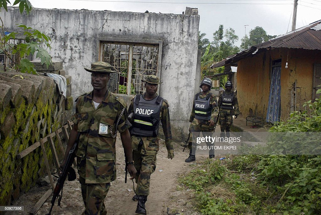 Military policemen walk past a building burnt by ethnic militias in search of arms and criminals at Omadino village in Warri South district of Niger Delta, 04 June, 2004. Security agencies have began house-to-house search for arms and criminals to check the menace of bandits and ethnic militias terrorising riverine communities and oil companies, who last April murdered two US expatriate oil workers and three navy troops in Niger Delta. AFP PHOTO PIUS
