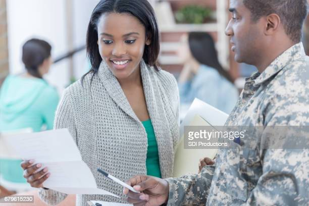military recruiter explains paperwork to new recruit - recruiter stock pictures, royalty-free photos & images