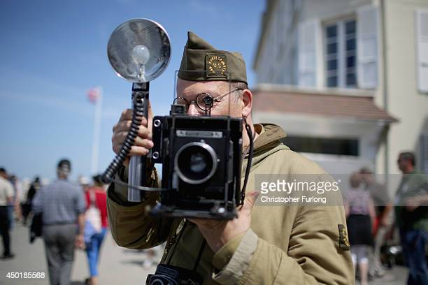 A military reenactor dressed as a war photographer takes part in the 70th anniversary of the DDay landings on June 6 2014 in Arromanches Les Bains...
