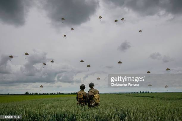 Military re-enactors look on as 280 paratroopers take part in a parachute drop onto fields at Sannerville on June 05, 2019 at Sannerville, France....