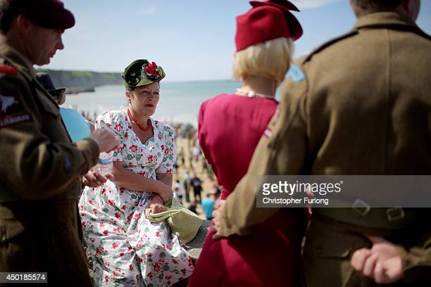 Military reenactors watch the ceremonies of the 70th anniversary of the DDay landings on June 6 2014 in Arromanches Les Bains France Friday 6th June...