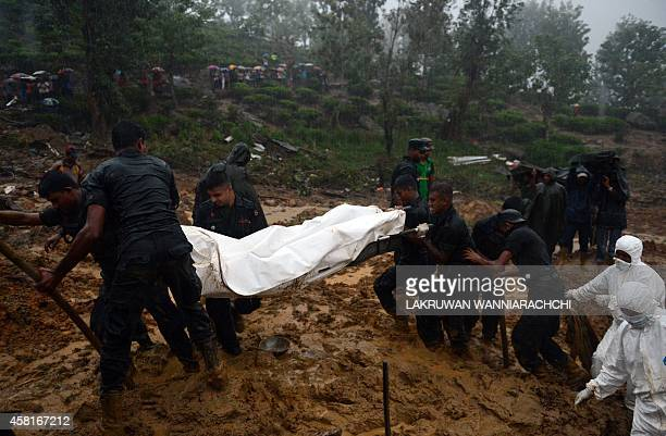 Military rescue workers recover the body of a woman who was buried alive with scores of others in the October 29 mudslide at a tea plantation in the...