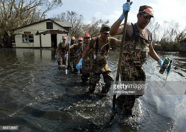 Military search and rescue crews wade through water after checking a house for any bodies on September 7 2005 in Port Sulfur Louisiana Hurricane...