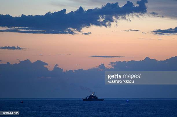 A military ship is pictured on the site of a shipwreck of migrants on October 6 2013 near the Lampedusa island three days after the tragedy Divers in...