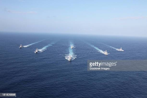 Military ships transit the Philippine Sea in formation.