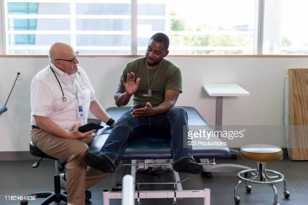 military soldier explains injury to doctor - injured soldier stock photos and pictures