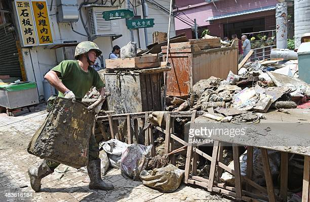 Military soldier helps clearing up debris in Wulai, the New Taipei City, on August 11, 2015. Taiwanese authorities were rushing to repair roads in...