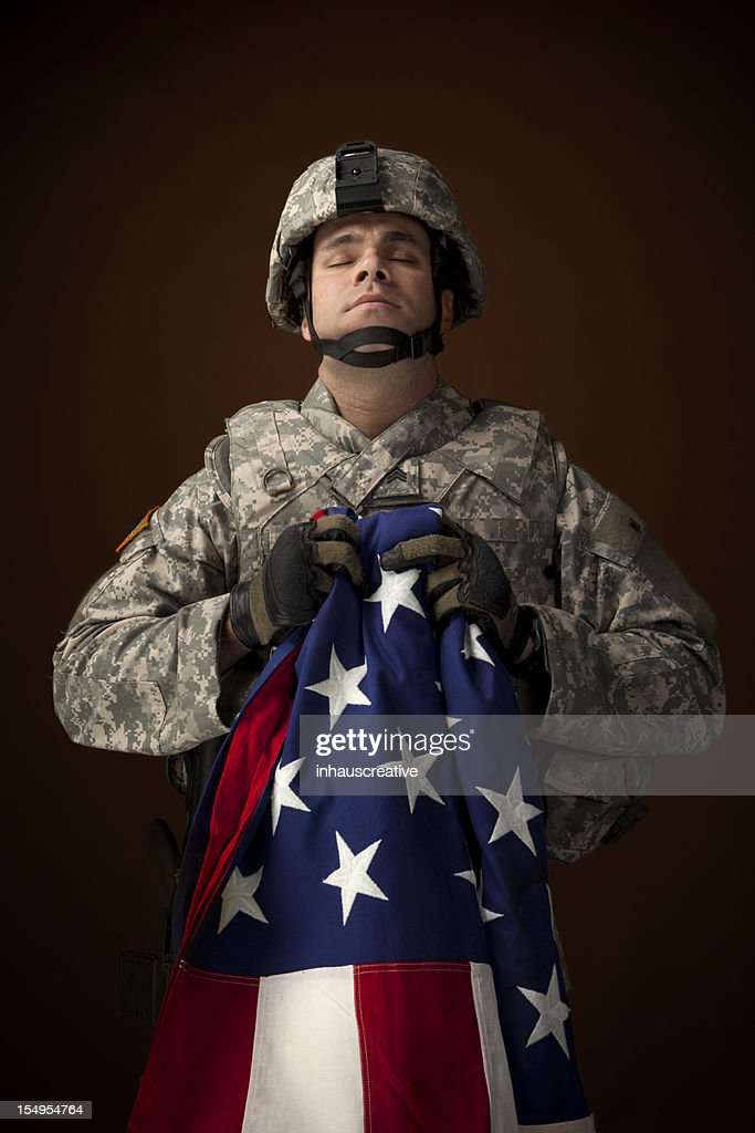 Military Soldier Praying and Hold an American Flag : Stock Photo