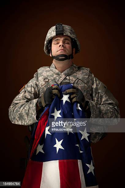 military soldier praying and hold an american flag - soldier praying stock photos and pictures