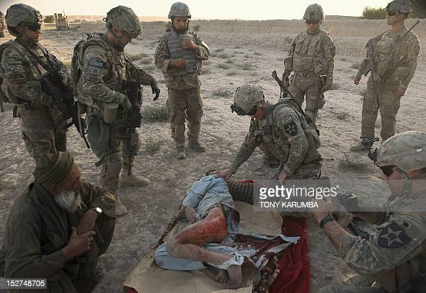 US military soldiers from the 3rd platoon Ccompany 123 infantry tend to a local Afghan man who was shot because he was suspected of being an...