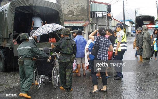 Military soldiers help to evacuate the warnning area's residents in eastern Hualien county on August 1, 2012. Taiwan shut down schools and cancelled...
