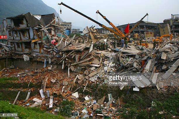 Military soldiers search of victims the debris of a dormitory of a collapsed chemical plant in at the Renhe Village May 15, 2008 in the outskirts of...