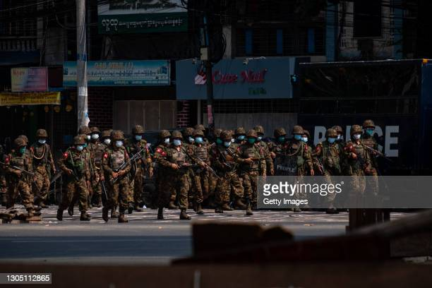 Military soldiers walk down a street while carrying weapons that contain live ammunition after clashes with protesterrs on March 03, 2021 in Yangon,...