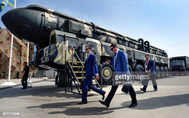 Military specialists walk past a Russian Topol intercontinental ballistic missile at the exposition field in Kubinka Patriot Park outside Moscow on...