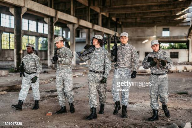 military squad patrolling through ruined building - military attack stock pictures, royalty-free photos & images