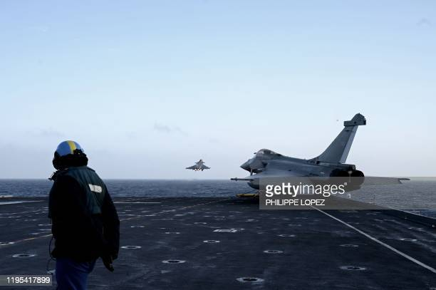 A military staff looks at Rafale jet fighters taking off the French aircraft carrier Charles de Gaulle at sea off the coast of the city of Hyeres on...