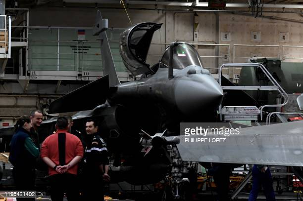 Military staff stand past a Rafale jet fighter on the French aircraft carrier Charles de Gaulle at sea off the coast of the city of Hyeres on January...