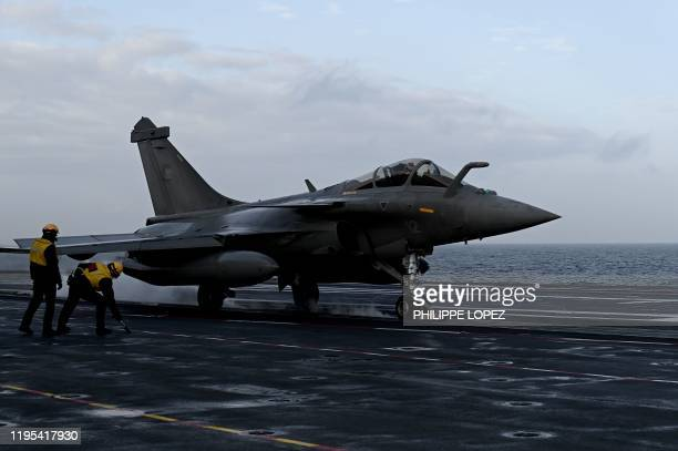 Military staff stand past Rafale jet fighter about to take off the French aircraft carrier Charles de Gaulle at sea off the coast of the city of...