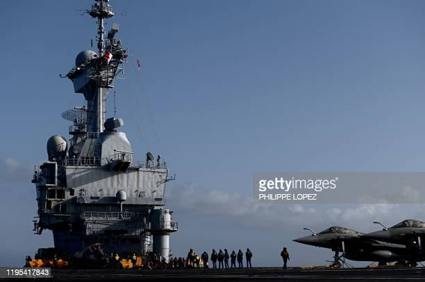Military staff stand past Rafale jet fighters on the deck of the French aircraft carrier Charles de Gaulle at sea off the coast of the city of Hyeres...