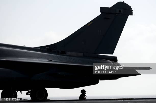 A military staff stands past a Rafale jet fighter on the deck of the French aircraft carrier Charles de Gaulle at sea off the coast of the city of...