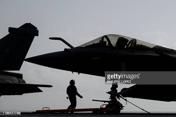A military staff stands past Rafale jet fighters about to take off from the French aircraft carrier Charles de Gaulle at sea off the coast of the...