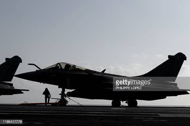A military staff stands past Rafale jet fighters on the deck of the French aircraft carrier Charles de Gaulle at sea off the coast of the city of...