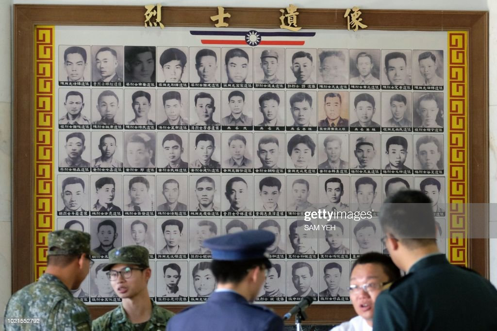 Military staff talk in front of portraits of deceased soldiers during the 60th anniversary of the '823 bombardment' in Kinmen on August 23, 2018. - The tiny Taiwanese island of Kinmen on August 23 marked the 60th anniversary of a Chinese artillery attack that killed hundreds of people, as cross-strait tensions rise once more.
