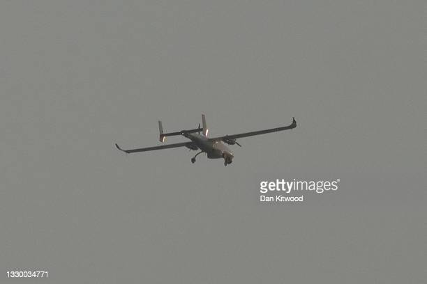 Military style drone passes over as migrant men, women and children cross the shipping lane in the English Channel on July 22, 2021 off the coast of...