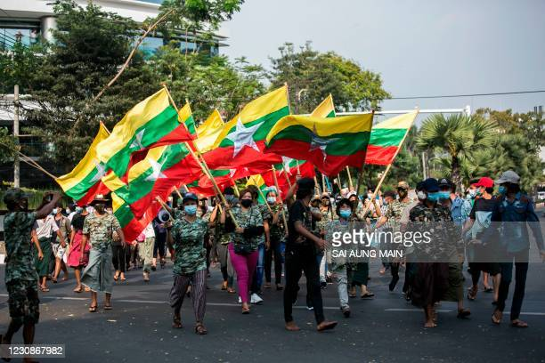 Military supporters carry Myanmar's national flags during a protest to demand an inquiry to investigate the Union Election Commission in Yangon on...