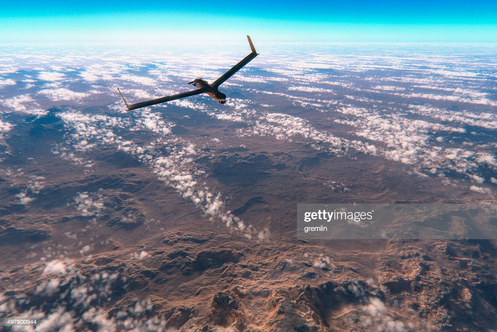 Military surveillance drone flying over rocky deserts : Stock Photo